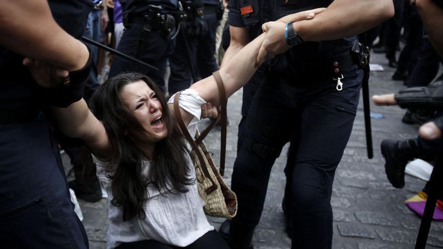 Una mujer es arrastrada por dos agentes en una concentración del pasado mes de junio en Madrid. Foto: Olmo Calvo