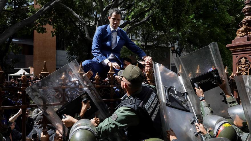 El líder de la oposición venezolana, Juan Guaidó, escala una valla en su intento por ingresar a la sede de la Asamblea Nacional, custodiada por la policía para evitar su entrada y la de los diputados de la oposición en Caracas (Venezuela) el pasado 5 de enero