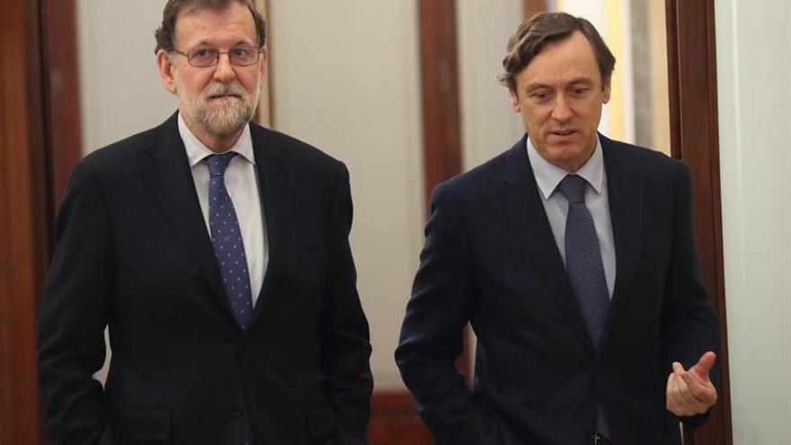 El presidente del Gobierno, Mariano Rajoy (i), junto al portavoz parlamentario del PP, Rafael Hernando (d), en los pasillos del Congreso de los Diputados