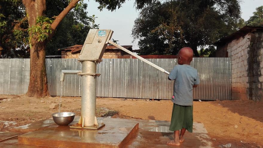 Un niño recoge agua en el sitio de desplazados ubicado en la Gran Mezquita de Pk5
