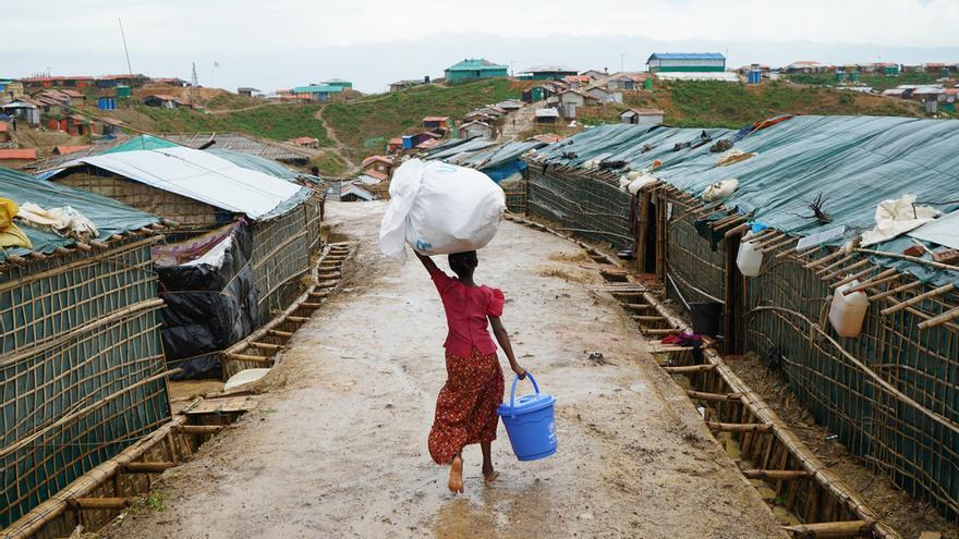 Una joven rohingya camina por las calles mojadas del campo de refugiados de Balukhali portando sobre su cabeza artículos de primera necesidad suministrados por la ONU. Un año después de su llegada, la gente sigue viviendo en refugios básicos precarios, lo que les deja en una situación muy vulnerable frente a las lluvias, el calor o el viento. Muchas tiendas fabricadas con láminas de plástico y bambú se han derrumbado o han sido arrastradas por las fuertes lluvias del monzón.