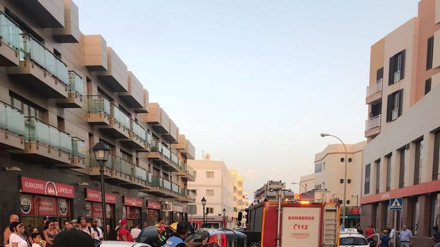Un vecino fotografía el coche volcado en la calle Triana de Arrecife de Lanzarote.