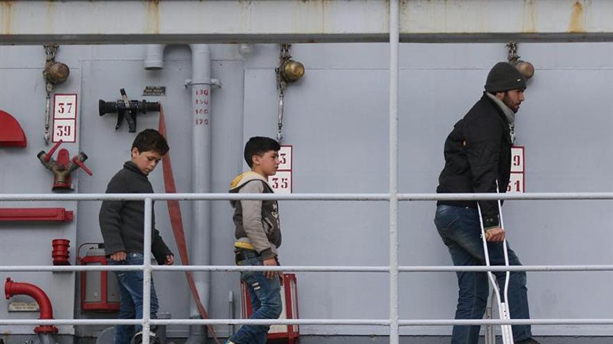 Algunos menores migrantes se disponen a desembarcar de un barco de la marina italiana en el puerto de Salerno, isla de Lampedusa, Italia, tras ser rescatados en aguas del Mediterráneo.