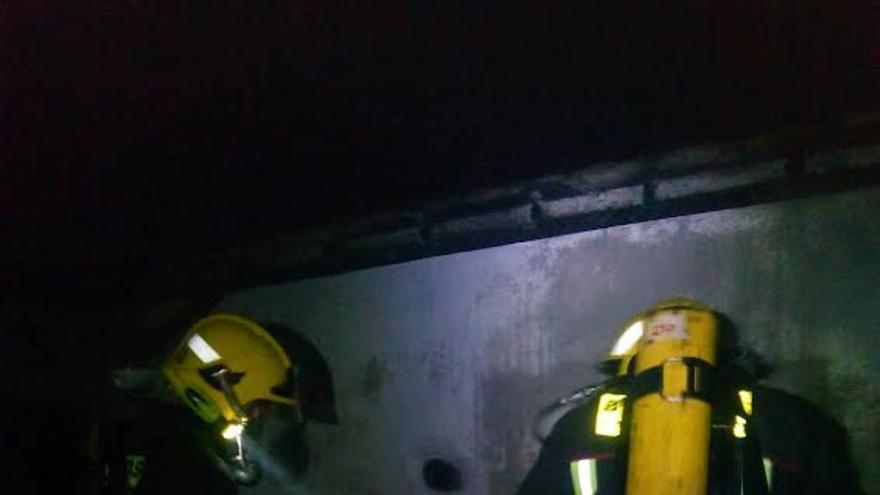 En la imagen, dos bomberos, en la noche de este viernes, durante las tareas de extinción del incendio en un casa de Garafía. Foto: BOMBEROS LA PALMA.