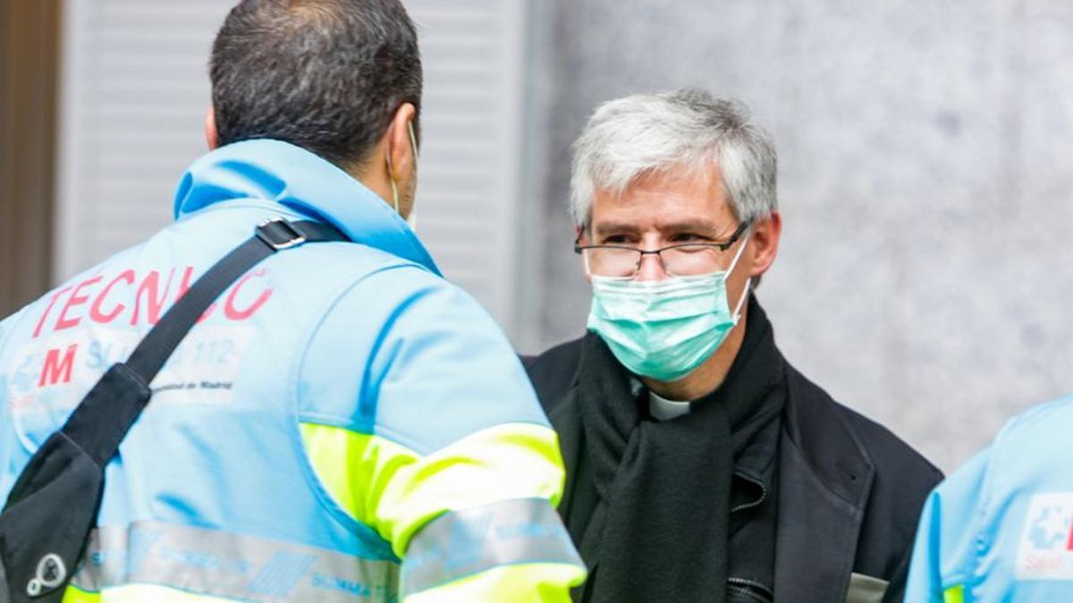 Un técnico sanitario habla con un sacerdote en el interior de un hospital público que atiende a pacientes COVID