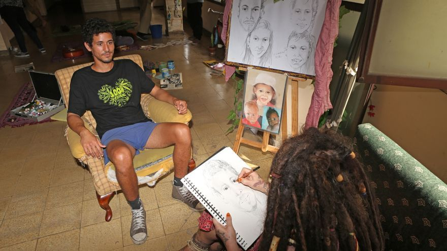 María, 'Rasta Mama', haciéndole un retrato a Ismael en el Centro Social La Bicicleta (ALEJANDRO RAMOS)