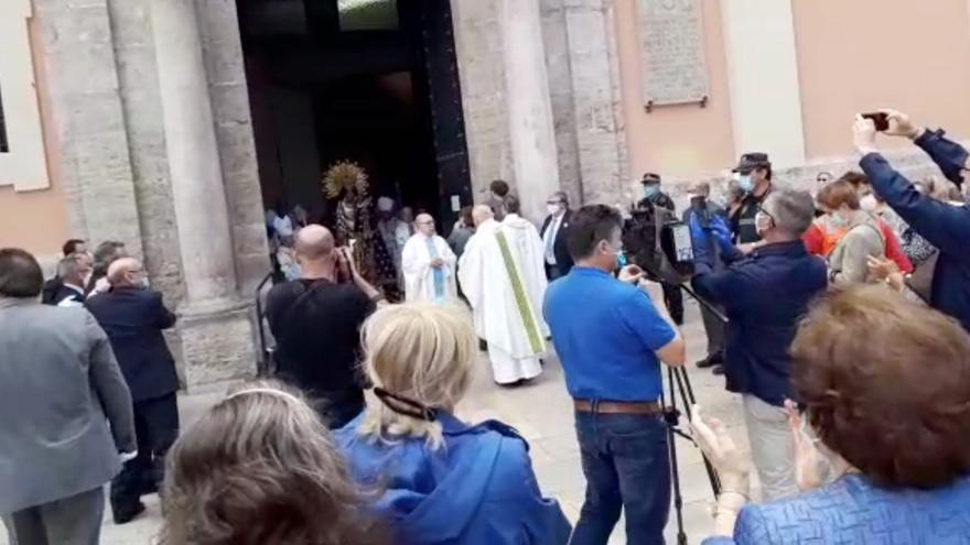 Momento en el que sale la celebración con la imagen de la Virgen de los Desamparados ante la expectación de decenas de personas.