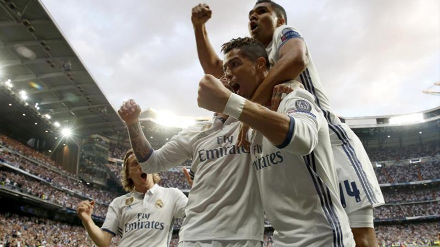 El delantero portugués del Real Madrid Cristiano Ronaldo (c) celebra uno de sus goles ante el Atlético de Madrid
