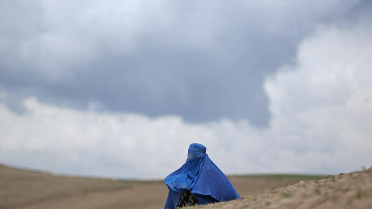 Una mujer sentada sola tras sobrevivir a un ataque contra su aldea en el noreste de Afganistán en 2014.