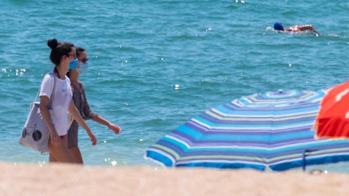 """Dos jóvenes pasean con la mascarilla por la playa de la """"Barriada de pescadores"""" en La Antilla (Huelva)."""