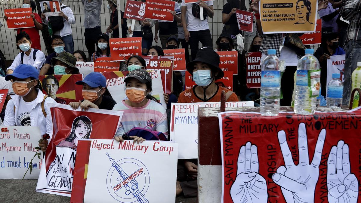 Manifestantes en Myanmar sujetan carteles contra el golpe de estado militar