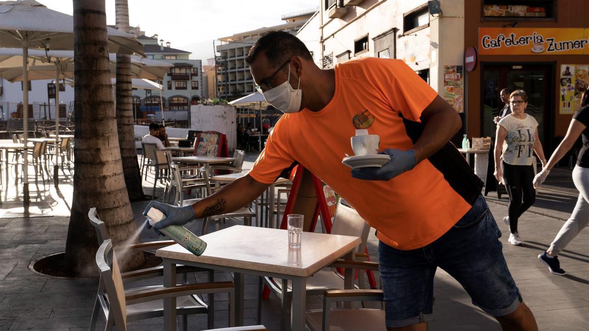 Un camarero desinfecta unas sillas de una terraza de un bar de Puerto de la Cruz, en Tenerife