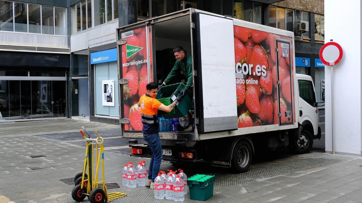 Dos repartidores de 'El Corte Inglés' descargan su mercancía durante el primer día laborable desde del estado de alarma decretado por el coronavirus en el país, en Palma