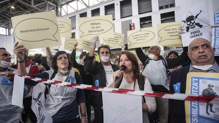 Un membre de Desmilitaritzem entrega una còpia de la moció 55/XI del Parlament de Catalunya