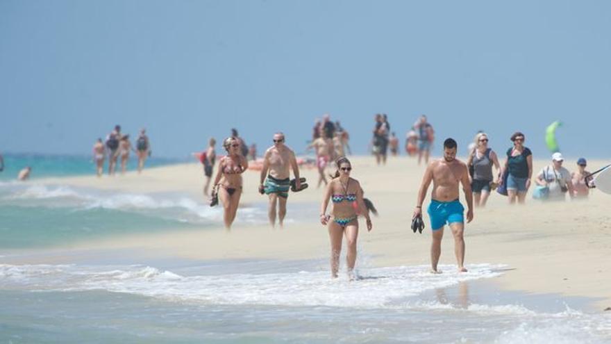 Turistas de paseo por la playa, en Canarias
