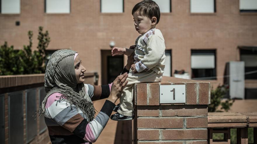 """Fatem junto a Ahmed en la puerta de su nueva vivienda: """"Quisiera poder brindarles  a mis hijos una vida estable. No podemos seguir huyendo de un país para otro"""". Foto: Pablo Tosco-Oxfam Intermón"""