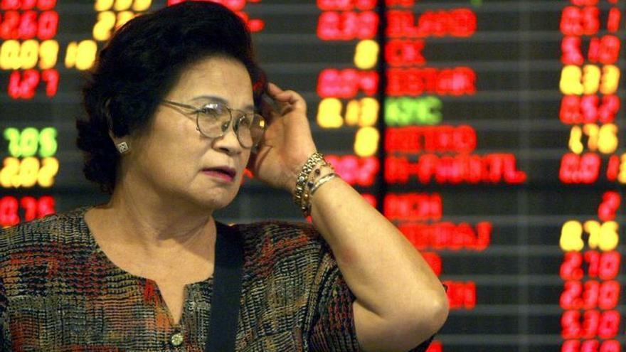 Una inversora tailandesa observa el panel de resultados bursátiles en el parqué de Bangkok (Tailandia).