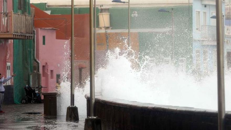 Un joven fotografía el fuerte oleaje en el barrio de San Cristóbal como consecuencia del temporal de viento que afecta a las Islas Canarias.
