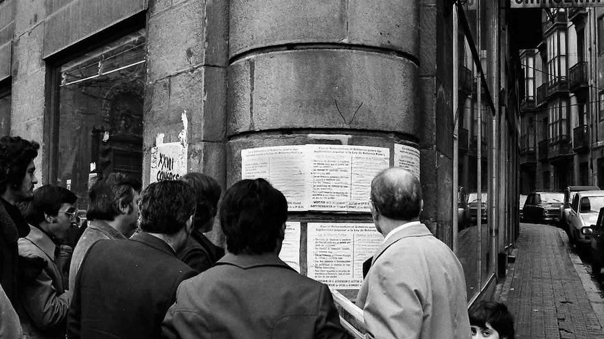 Ciudadanos se paran delante de la cartelería de la época. Foto: Mikel Alonso.