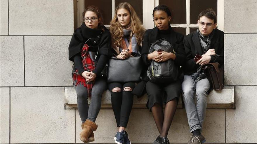 Estudiantes sentados en el voladizo de una ventana se suman al minuto de silencio celebrado en la Universidad de la Sorbona en memoria de las víctimas mortales de los atentados del pasado viernes en París