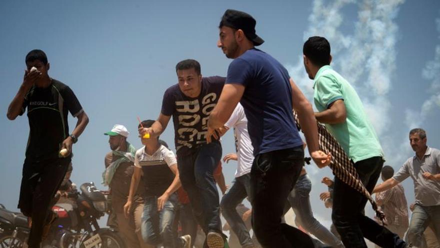 Manifestantes palestinos huyen del ejército israelí durante las protestas en la frontera entre Gaza e Israel.