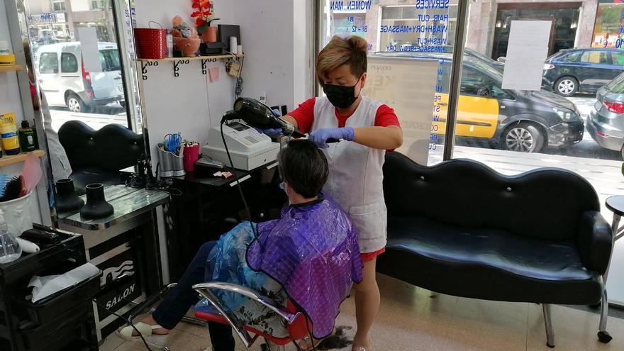 Xu corta el pelo a una clienta este lunes