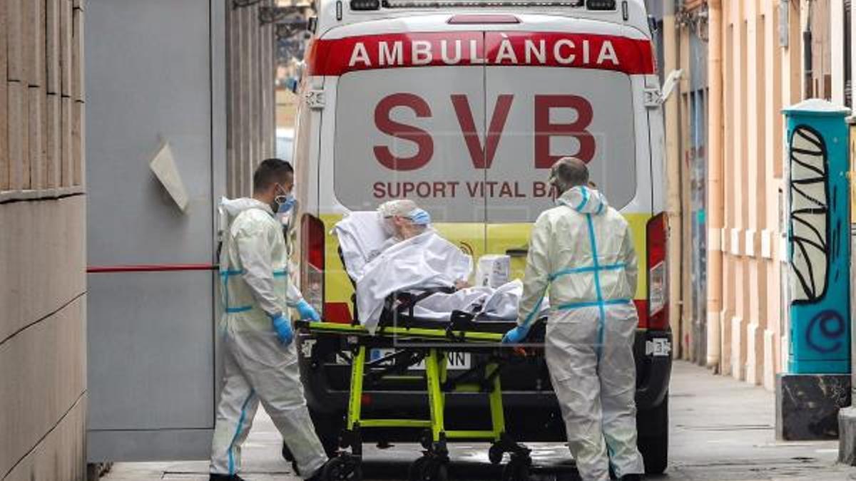 Personal sanitario se dispone a trasladar a un enfermo de COVID-19 en una ambulancia.