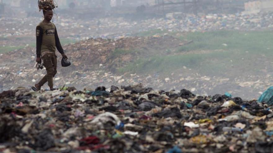 Un hombre transporta cables sobre su cabeza en el mayor vertedero de basura electrónica del continente africano.