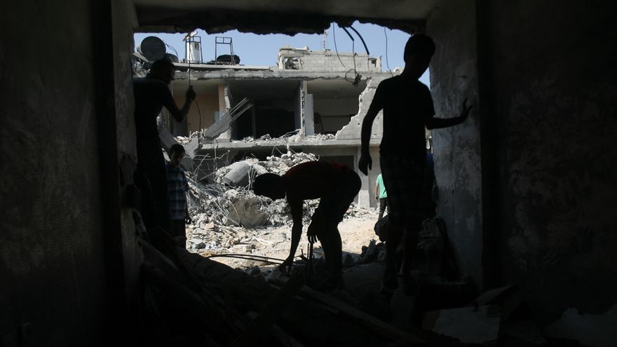 Unos jóvenes recorren las ruinas de su casa destruida en Rafá, Gaza, buscando algo que se pueda salvar. Foto Eyad Al Baba/Zuma Press.