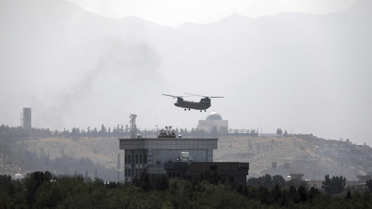 Un helicóptero Chinook de Estados Unidos vuela sobre la Embajada de Kabul, en Afghanistan. Los helicópteros están aterrizando en la embajada mientras vehículos diplomáticos la abandonan el avance talibán. AP Photo/Rahmat Gul