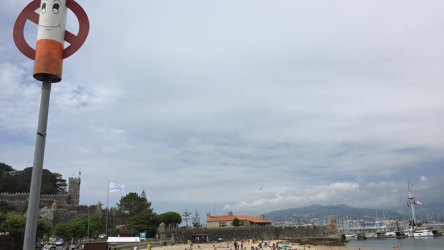 Vista de la playa de la Ribeira, en Baiona, con una de las figuras que la identifica como playa sin humos