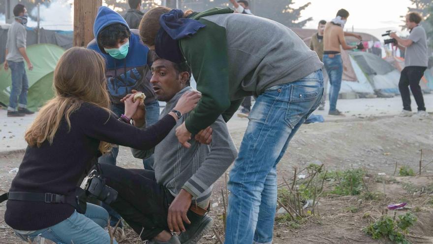 Varios voluntarios atienden a un afectado por los gases lacrimógenos en el campo de Idomeni   FOTO: Pablo Gabande