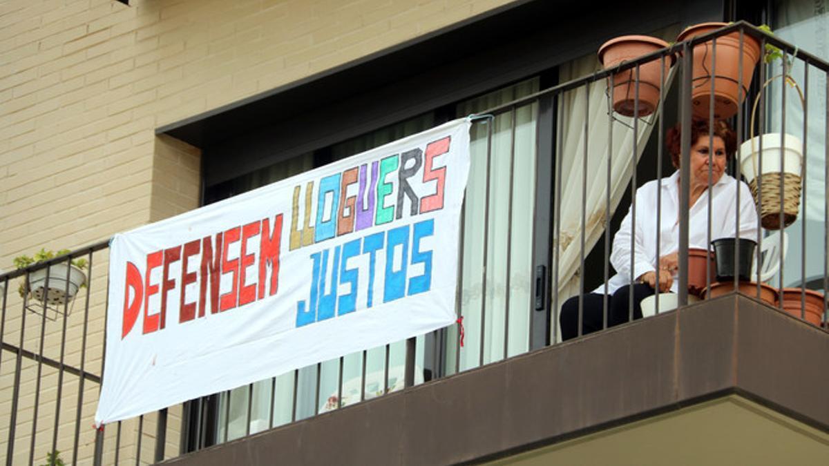 """Una mujer mira desde un balcón con una pancarta por los """"alquileres justos"""""""