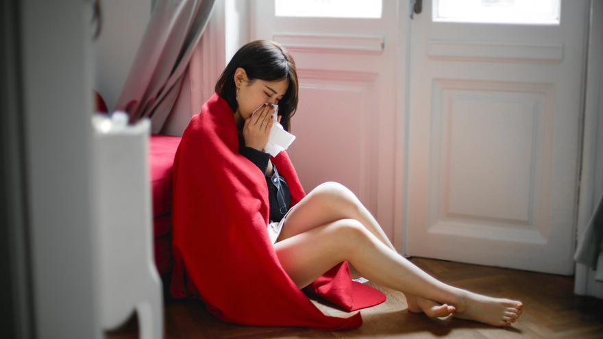 Una mujer estornuda mientras está sentada en el suelo.