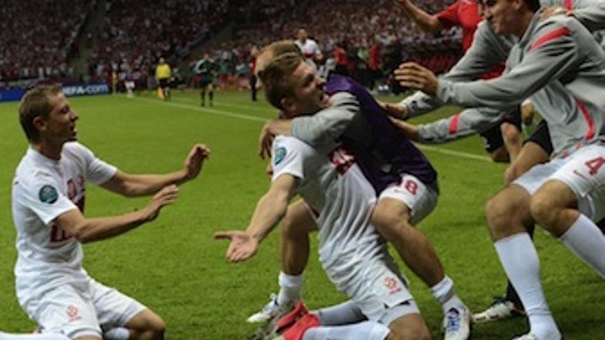 Los polacos abrazan a Blaszczykowski tras lograr la igualada. (es.uefa.com)