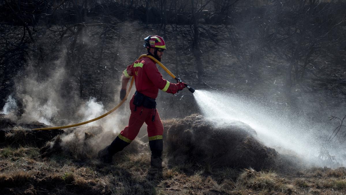 Un efectivo de la Unidad Militar de Emergencias refresca el perímetro de un incendio forestal en Cualedro (Ourense) el pasado mes de septiembre
