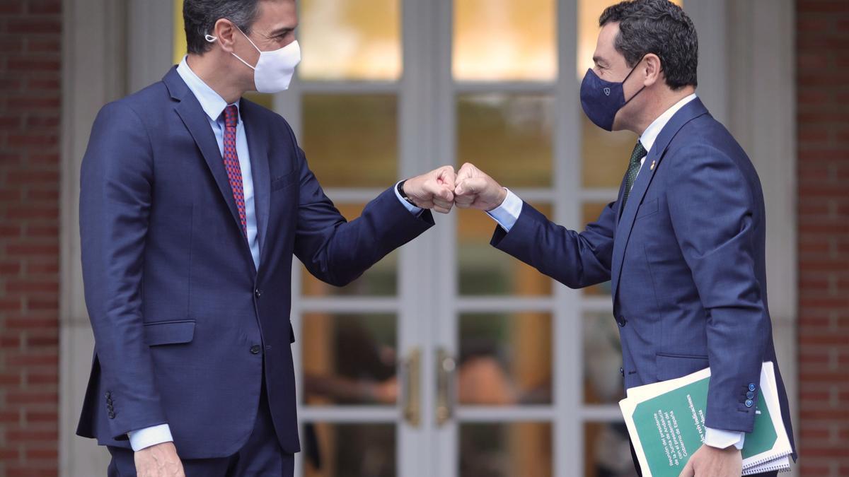 El presidente del Gobierno, Pedro Sánchez (i), saluda con el puño al presidente de la Junta de Andalucía, Juan Manuel Moreno Bonilla, a su llegada al Palacio de la Moncloa, a 17 de junio de 2021. Se trata de la primera reunión oficial de ambos mandatarios