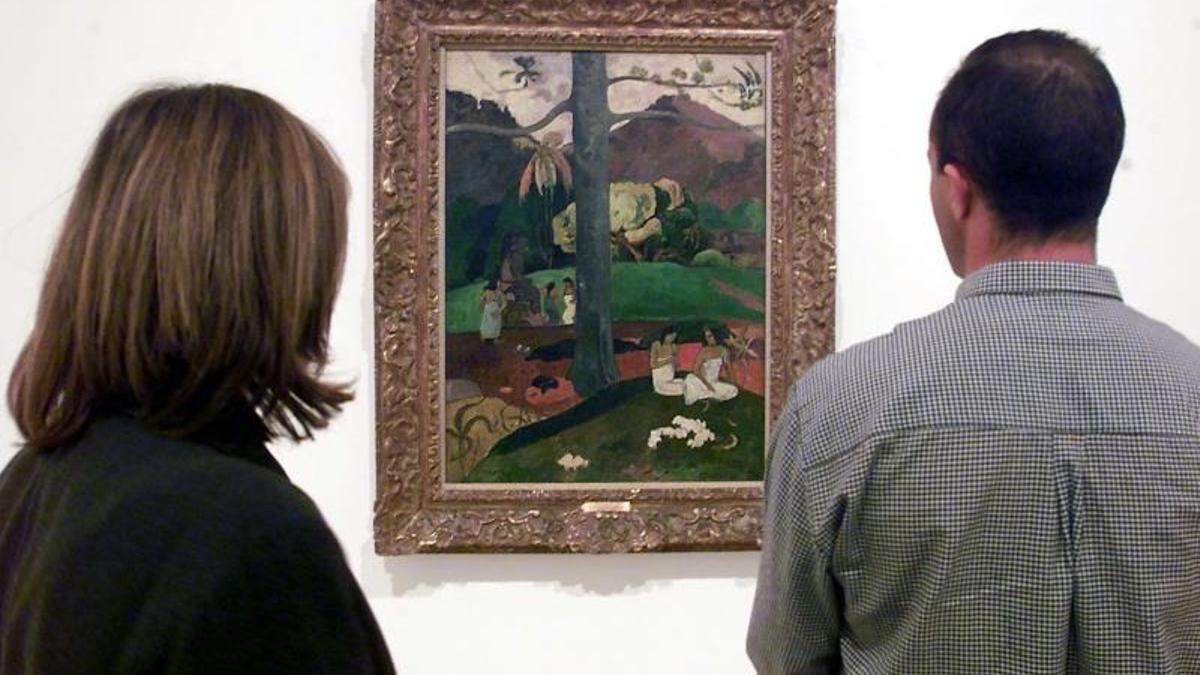 """Dos visitantes observan el cuadro """"Mata Mua"""" de Paul Gauguin."""