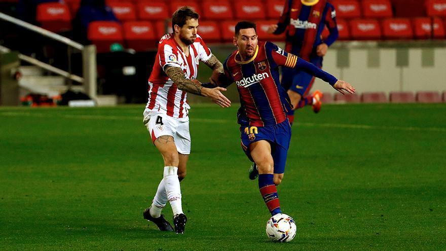 Íñigo Martínez se disputa un balón con Leo Messi