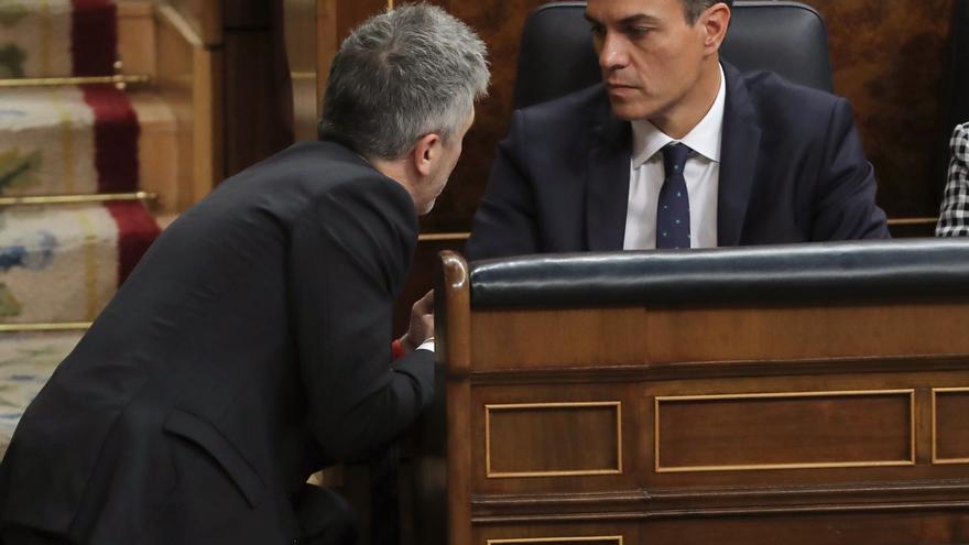 El ministro Grande-Marlaska charla con Pedro Sánchez en la bancada del Gobierno en el Congreso