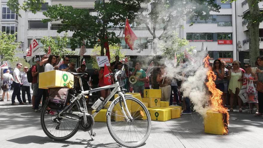 Los miembros de CCOO han prendido fuego a una caja de cartón que simbolizaba una de las mochilas de Glovo.
