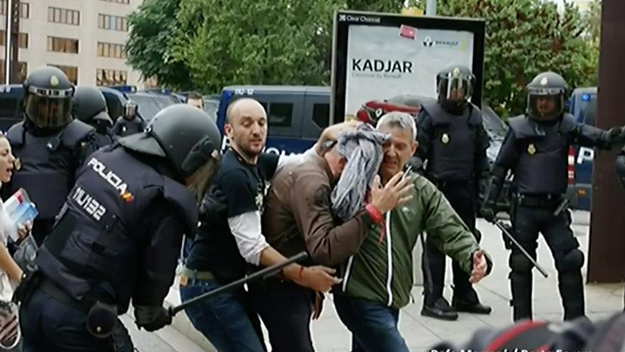 Un policía golpea a una persona que ayuda a un herido el 1-O en una foto aportada por la defensa.
