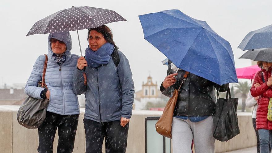 Varias personas se protegen de la lluvia en el Puente Romano | ÁLEX GALLEGOS