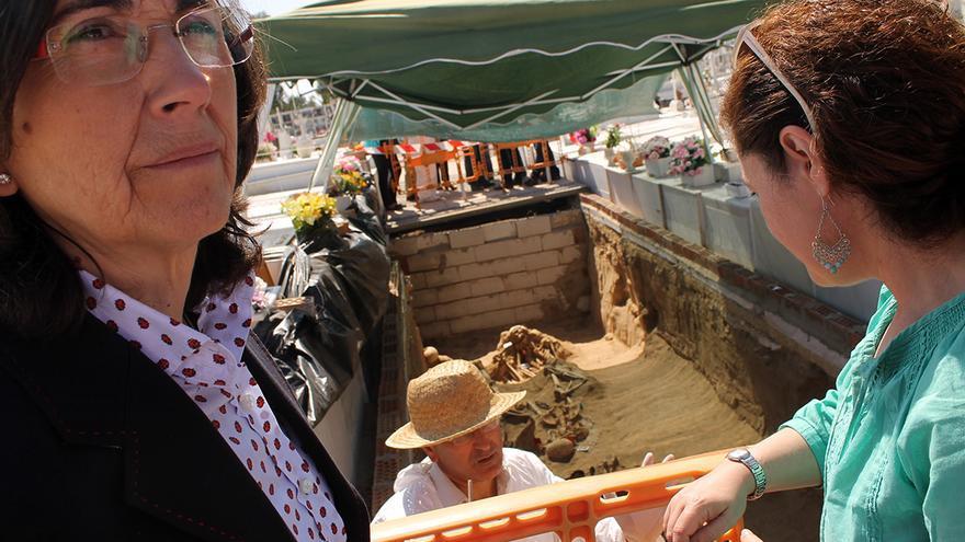 La consejera de Cultura, Rosa Aguilar, y la diputada de IU, Inmaculada Nieto, junto a la fosa de Puerto Real. / JUAN MIGUEL BAQUERO