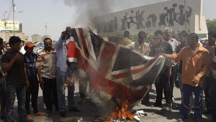 Protestantes queman una bandera británica por el asesinato de Baha Mousa en la plaza de Tahrir en Baghdad, Irak
