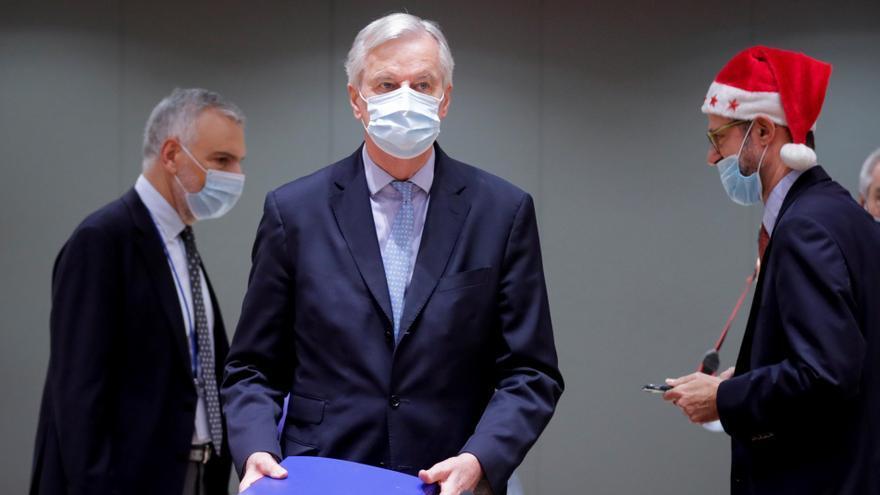 El negociador comunitario Michel Barnier (c) deposita en la mesa el archivador con las 2.000 páginas del acuerdo alcanzado con el Reino Unido en presencia de delegados griegos durante la reunión extraordinaria convocada este viernes en Bruselas para explicar los detalles del acuerdo del brexit. EFE/Olivier Hoslet