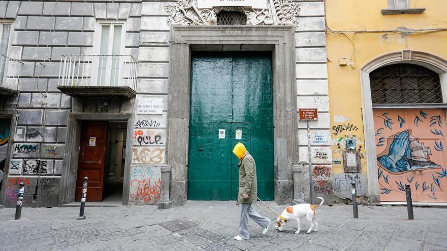 Un hombre pasea a su perro por una calle vacía de Nápoles en medio del brote de coronavirus en Italia.
