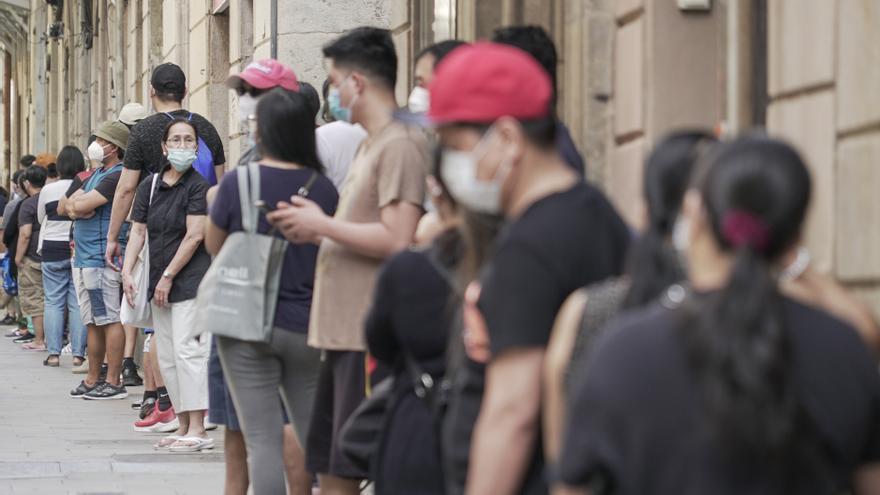 La comunidad filipina hace largas colas para esperar a recibir la comida, en el Raval de Barcelona
