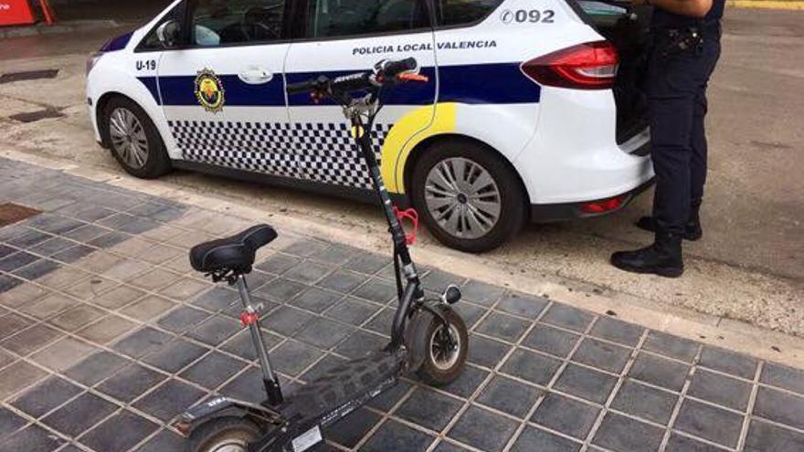Un agente de la Policía Local de València junto a un patinete eléctrico