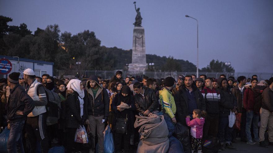 Refugiados aguardan el ferry a escasos metros de la estatua de la libertad del puerto de Mitilene, Lesbos / Foto: Olmo Calvo